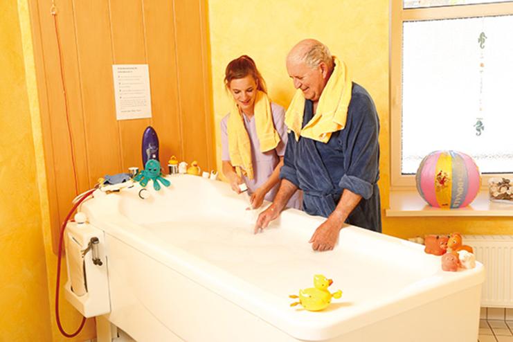 Senior mit Pflegekraft vor der Badewanne