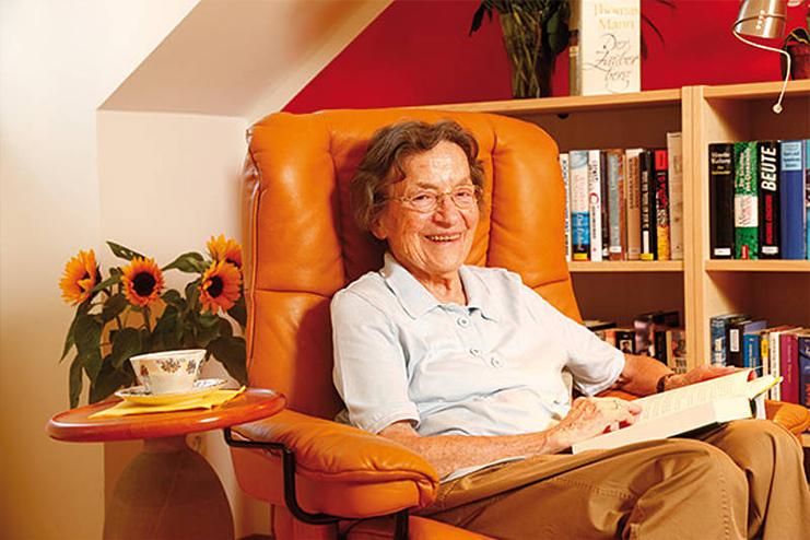 Ein Seniorin sitzt mit einem Buch im Sessel